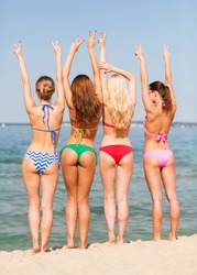 summer vacation, holidays, gesture, travel and people concept - group of young women showing peace or victory sign on beach from back