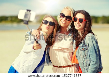 summer vacation, holidays, technology and people concept- group of smiling young women taking picture with smartphone on selfie stick on beach #1537741337