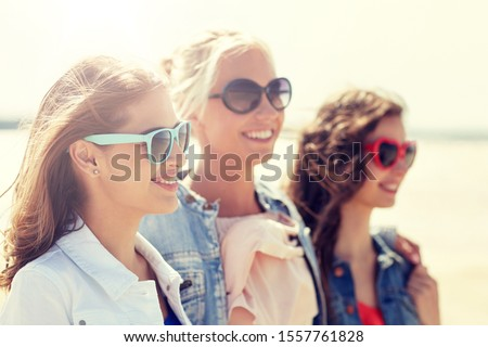 summer vacation, holidays, travel and people concept - group of smiling young women in sunglasses and casual clothes on beach #1557761828