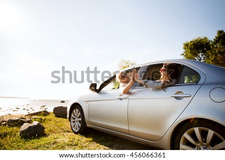 summer vacation, holidays, travel, road trip and people concept - happy teenage girls or young women in car at seaside making high five gesture #456066361