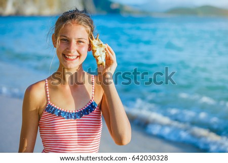Summer vacation. Listening to the sea - beautiful girl with shell at the beach #642030328