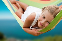 Summer vacation - lovely girl in colorful hammock