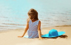 Summer vacation, lovely girl resting on the beach near water