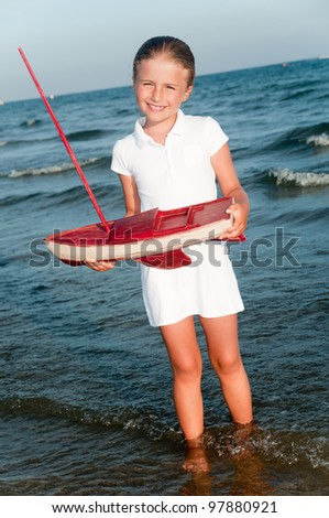 Summer vacation - lovely girl with yacht model on the beach - stock photo