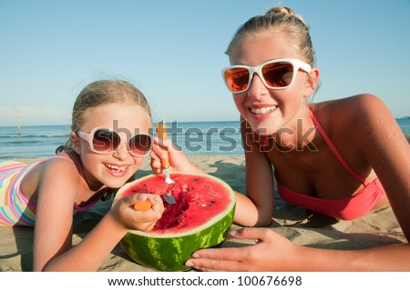 Summer vacation - lovely girls eating fresh watermelon on sandy beach