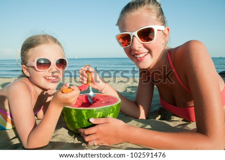 Summer vacation - lovely girls eating fresh watermelon on sandy beach