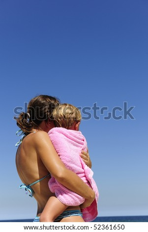 summer vacation on the beach: mother carrying her daughter