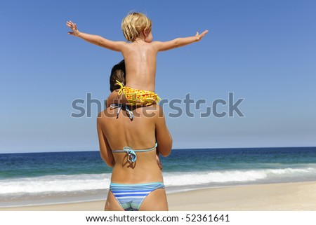 summer vacation on the beach: mother carrying her daughter on her shoulders
