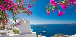 Summer vacation panorama, luxury famous Europe destination. White architecture in Santorini, Greece. Perfect travel scenery with pink flowers and cruise ship in sunlight and blue sky. Amazing view