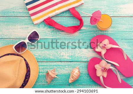 Summer vacation. Pink sandals and beach accessories. Blue wooden texture . Flat mock up for design. Beautifully toned image