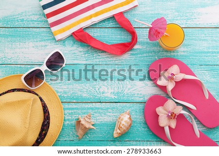 Summer vacation. Pink sandals and beach accessories on wooden background. Flat mock up for design.
