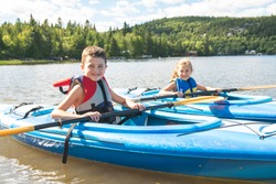 Summer vacation Portrait of cute boy and girl kayaking the on river