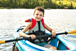 Summer vacation Portrait of happy cute boy kayaking the on river
