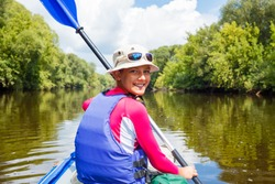 Summer vacation - Portrait of happy cute girl kayaking the on river, enjoying a lovely summer day
