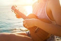 Summer Vacation. Smellingcaucasian women relaxing and playing on ukulele on beach, so happy and luxury in holiday summer, outdoors sunset sky background. Travel and lifestyle Concept.