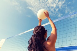 summer vacation, sport, leisure and people concept - young woman with ball playing volleyball on beach