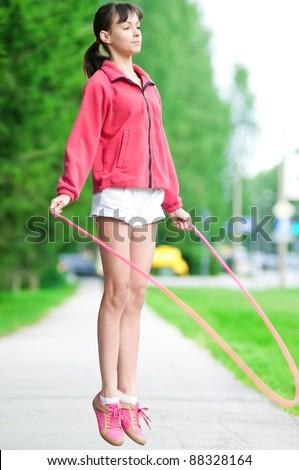 Summer vacation - teenage girl with skipping rope at park
