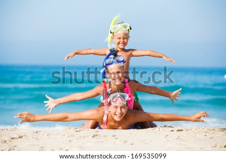 Summer vacation - Three happy children on beach with colorful face masks and snorkels, sea in background.