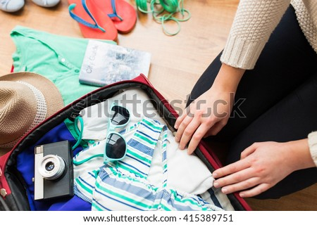 summer vacation, travel, tourism and objects concept - close up of woman packing travel bag for vacation #415389751
