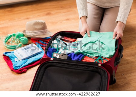 summer vacation, travel, tourism and objects concept - close up of woman packing travel bag for vacation