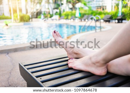 Summer Vacation. Woman feets on the wooden chair in the swimming pool.