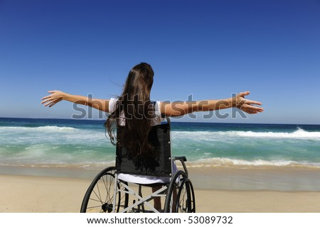 summer vacation: woman in wheelchair enjoying outdoors beach