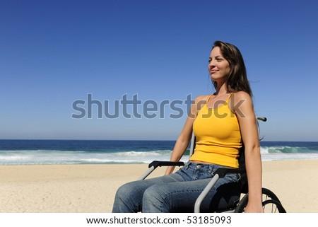 summer vacation: woman in wheelchair  enjoying outdoors beach - stock photo