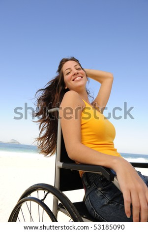 summer vacation: woman in wheelchair  sunbathing outdoors beach