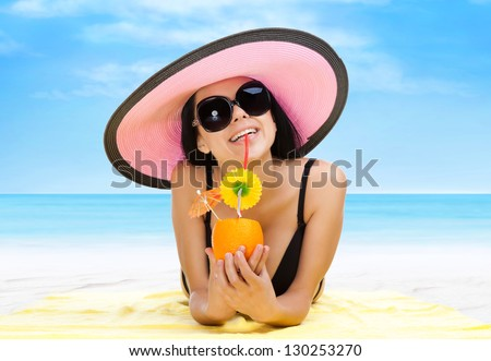 summer vacation woman lying on beach yellow sand towel smile drink tropical cocktail with straw, sun tanned body, girl wear pink hat, sunglasses, over sea blue sky, concept holiday travel