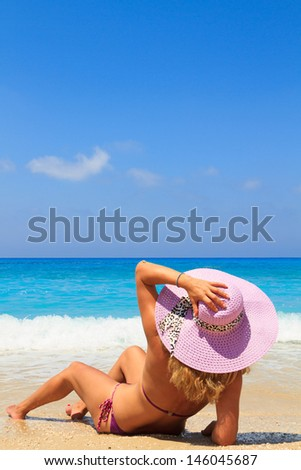 Summer vacation woman on the beach in beach hat enjoying summer holidays looking at the ocean #146045687