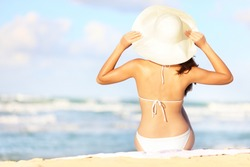 Summer vacation woman sitting on beach holding beach hat enjoying summer holidays looking at the ocean. Beautiful back side of model in bikini sitting down.