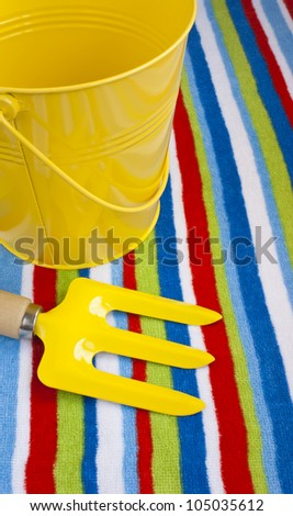 Summer vacations at the seaside, stripy beach towel, yellow bucket and fork.