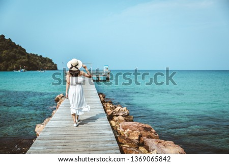 Summer vacations concept, Happy travel asian woman with white dress relax and walk on wooden bridge in tropical beach, Thailand