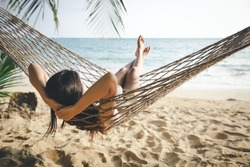 Summer vacations concept, Happy woman with white bikini, hat and shorts Jeans relaxing in hammock on tropical beach at sunset, Koh mak, Thailand