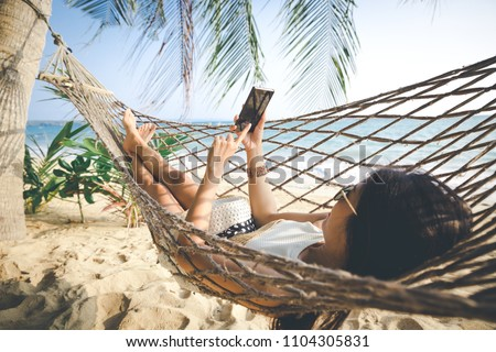 Summer vacations concept, Happy woman with white bikini, hat and sunglass using mobile phone in hammock on tropical beach at sunset, Koh mak, Thailand