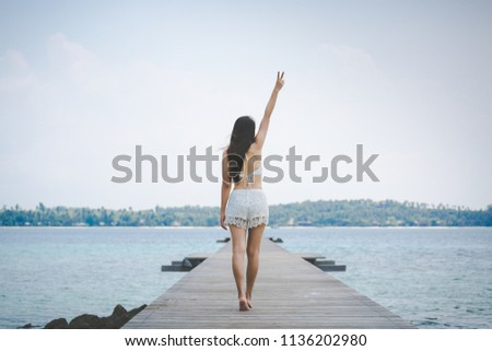 Summer vacations concept, Happy woman with white bikini relax and arms up v sign on wooden bridge in tropical beach, Thailand