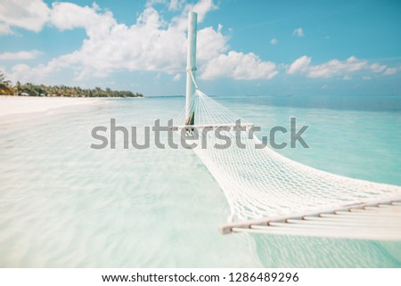 Summer vacations concept. Relaxing in hammock or swing on tropical beach at sunny day, amazing summer beach vacation and holiday background