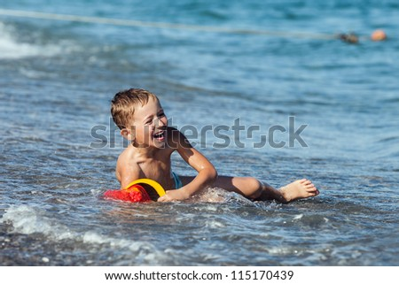 Summer vacations - little smiling child boy playing on sea sand beach