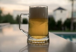 Summer vibes. Closeup view of cold beer mug on the table. The foam, golden liquid and glass on the table in the garden at sunset.