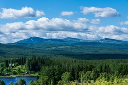 Summer view from a remotely located village in the Swedish highlands, with mountain tops and large pine and fir forests