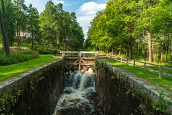 Summer view of a lock chamber with flushing water at a sluice along the Stromsholms canal in Sweden. With lush green trees along the canal