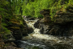 Summer view of a small creek in northern Sweden, flushing through eroded rock in a lush green forest