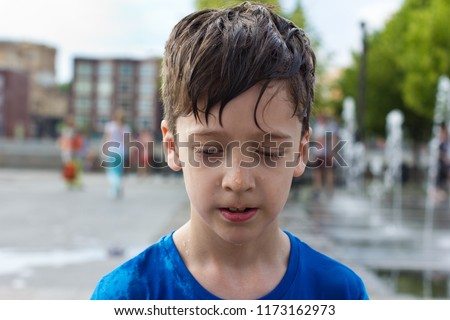 Summer walk. Wet boy on the background of fountains #1173162973
