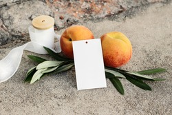 Summer wedding  or birthday still life scene. Closeup of blank gift tag mock-up. Olive branches, silk ribbon and peaches fruit on grunge concrete background. Seasonal sale concept, no people.