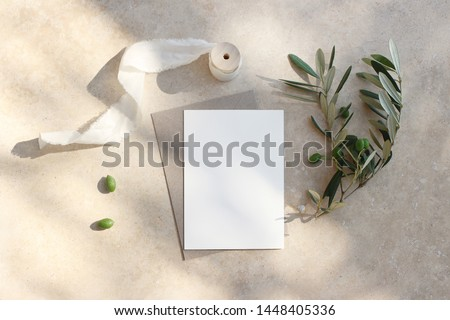 Summer wedding stationery mock-up scene. Blank greeting card, invitation. Craft envelope, olive fruit, branch and silk ribbon. Elegant marble background in sunlight, shadows. Flat lay, top view.