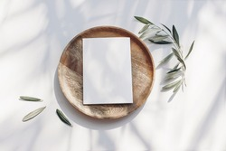 Summer wedding stationery mock-up scene. Blank greeting card, wooden plate, olive tree leaves and branches in sunlight. White table  background with palm shadows. Feminine flat lay, top view.
