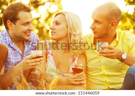 Summer weekend concept. Portrait of happy group of friends in trendy casual clothing drinking red wine, talking and having fun. Sunny day. Outdoor shot