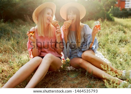 Summer weekend in countryside.  Two friends  having fun and  enjoying picnic in the park.  Drinking wine. Straw har, pastel colors. Sunset.