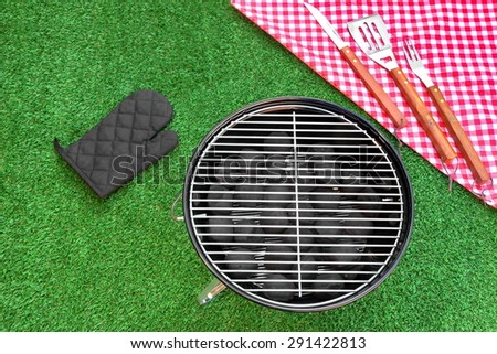 Summer Weekend Or Holiday BBQ Grill Party Or Picnic Concept. Park Or Backyard Fresh Lawn In the Background. Portable Kettle Charcoal Grill And Tools Close-up