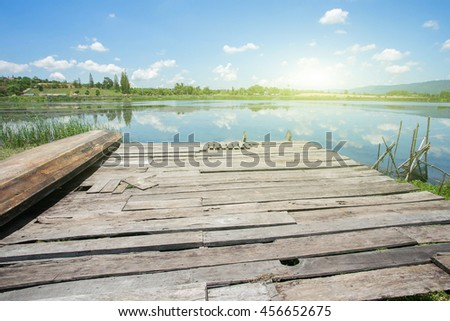 Summer wild landscape of beautiful wooden bridge extending into the lake and reflection of blue sky in the water in day light with effect light added. #456652675